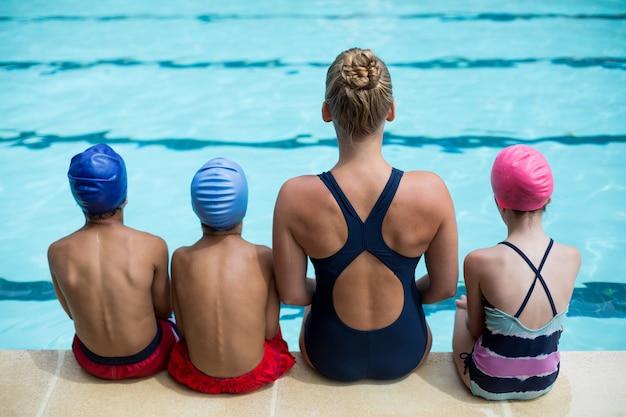 Vue arrière de l'instructrice enseignant aux enfants au bord de la piscine