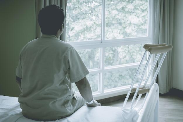 Vue arrière de la jambe de l'homme du patient utilise des béquilles pour marcher après une blessure de récupération chirurgicale des os cassés