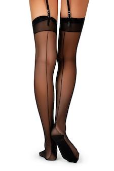 Vue arrière des jambes féminines en bas couture noirs avec porte-jarretelles isolé on white