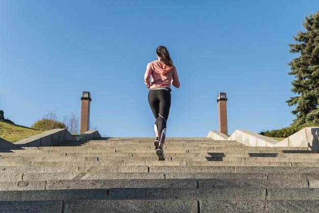 Vue arrière jeune athlète courir en plein air