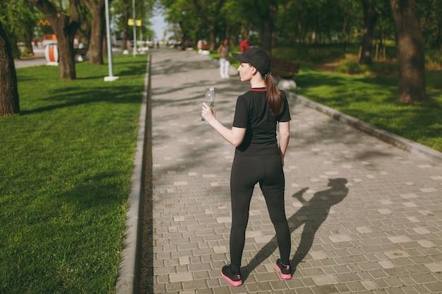 Vue arrière de la jeune belle fille brune athlétique en uniforme noir et casquette tenant une bouteille, avec de l'eau pendant l'entraînement avant de courir debout dans le parc de la ville à l'extérieur