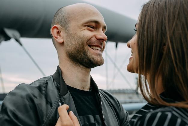Vue arrière d'un jeune couple assis sur le côté d'un lac touchant la tête amoureux.