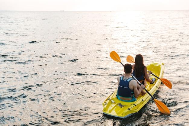 Vue arrière d'un jeune couple attrayant kayak