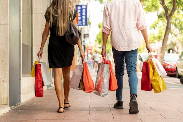 Vue arrière jeune couple marchant avec des sacs