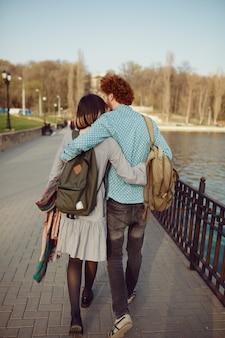 Vue arrière jeune couple avec sacs à dos marcher sans soucis dans le parc près du lac