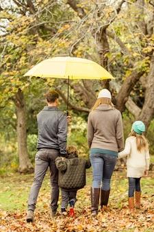 Vue arrière de la jeune famille sous le parapluie