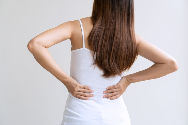 Vue arrière de la jeune femme asiatique souffrant de maux de dos isolé sur fond blanc. fermer