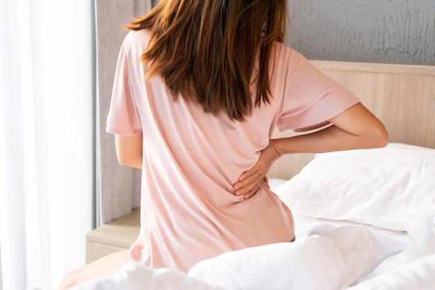Vue arrière de la jeune femme asiatique souffrant de maux de dos sur le lit le matin.