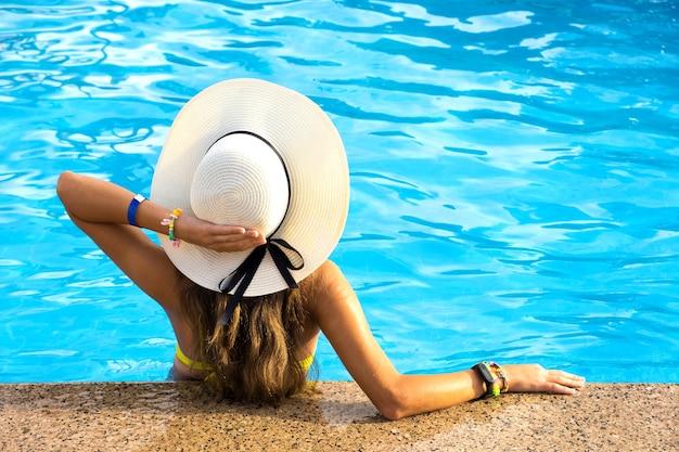 Vue arrière de la jeune femme aux cheveux longs portant un chapeau de paille jaune se détendre dans la piscine d'été chaude avec de l'eau bleue sur une journée ensoleillée.