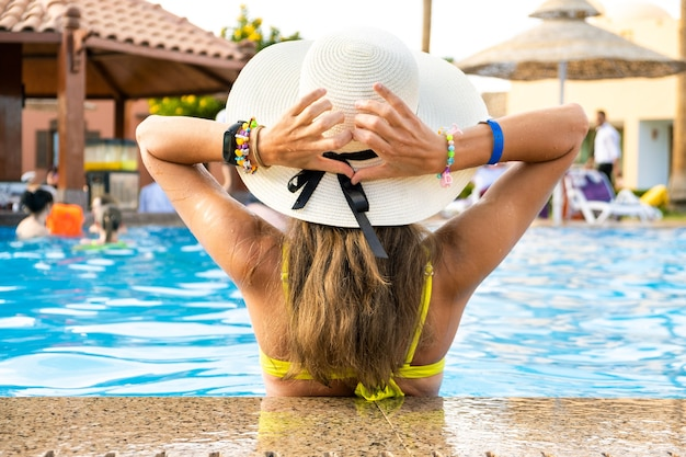Vue arrière d'une jeune femme aux cheveux longs portant un chapeau de paille se relaxant en été dans la piscine de l'hôtel avec de l'eau bleue par une journée ensoleillée.