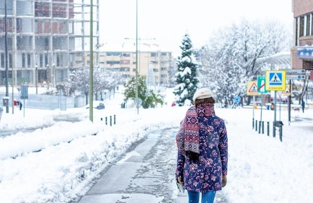 Vue arrière d'une jeune femme blonde vêtue de vêtements d'hiver marchant le long d'une avenue enneigée de la ville.