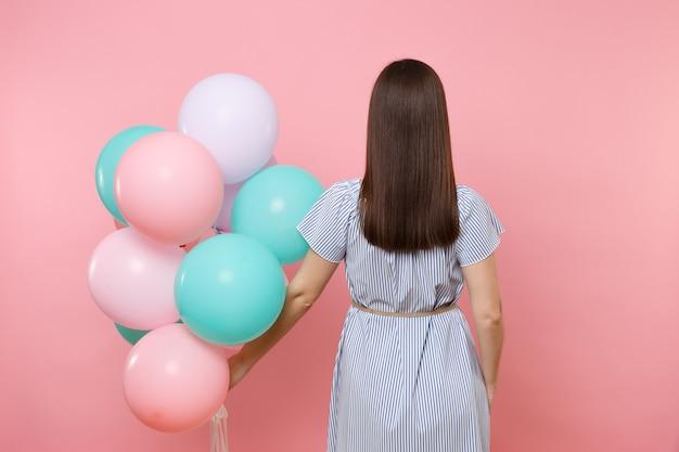 Vue arrière de la jeune femme brune vêtue d'une robe à rayures bleues tenant des ballons à air colorés isolés sur un fond rose tendance lumineux. fête d'anniversaire, concept d'émotions sincères.