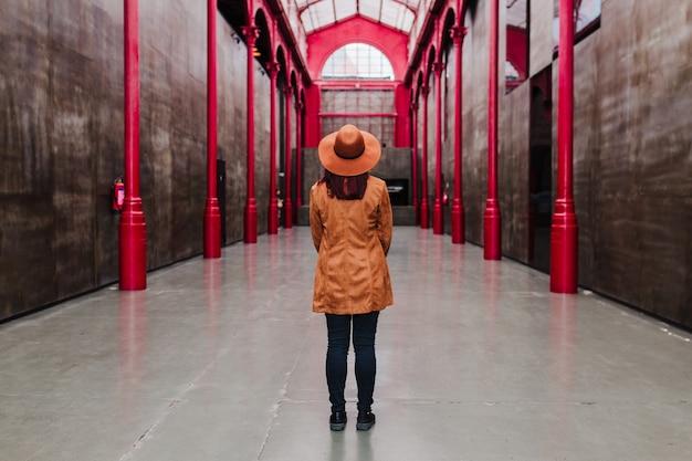 Vue arrière de la jeune femme caucasienne à l'extérieur sur la construction de colonnes rouges. concept de voyage