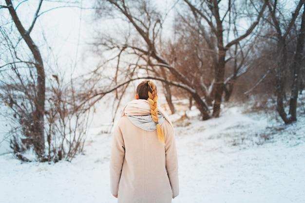 Vue arrière de la jeune femme avec une coiffure tresse portant un manteau sur les arbres enneigés de la forêt.