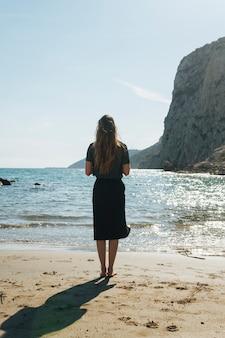 Vue arrière de la jeune femme debout sur la magnifique plage
