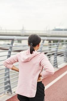 Vue arrière d'une jeune femme debout sur un stade de sport et s'entraînant seule à l'extérieur