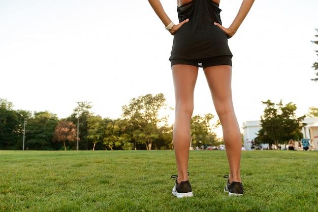 Vue arrière d'une jeune femme fitness dans les écouteurs