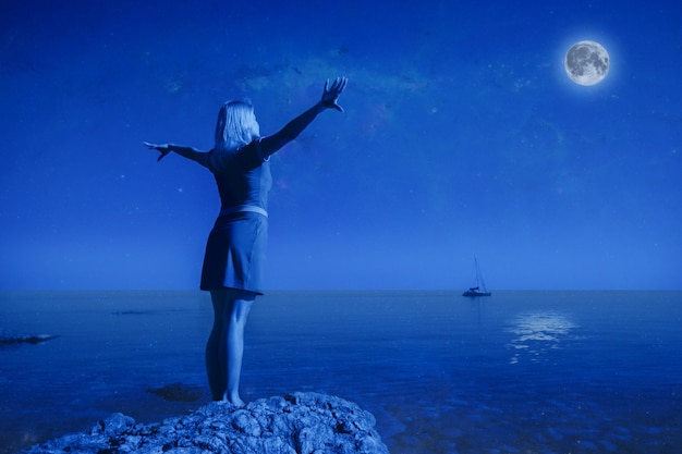 Vue arrière une jeune femme heureuse non identifiée se dresse sur une pierre lever les mains en regardant la grande lune et l'eau de mer claire et calme sur fond de paysage et de ciel nocturne clair. notion de pleine lune