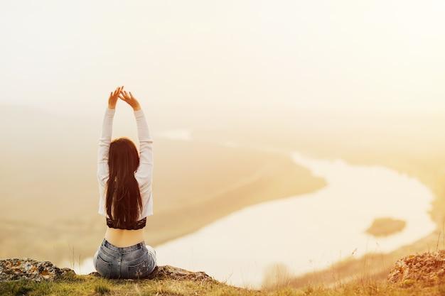 Vue arrière de la jeune femme levant les bras vers le ciel.
