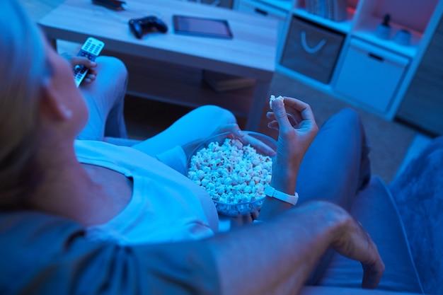 Vue arrière de la jeune femme mangeant du pop-corn pendant que son petit ami l'embrassant sur le canapé, ils regardent un film ensemble