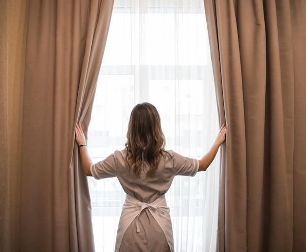 Vue arrière d'une jeune femme de ménage ouvrant des rideaux dans une chambre d'hôtel