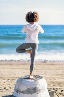 Vue arrière de la jeune femme noire, faire du yoga sur la plage