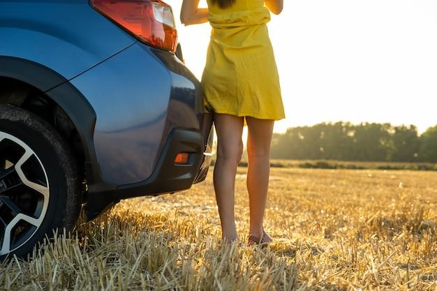 Vue arrière de la jeune femme pilote jambes minces en courte robe d'été jaune debout près de sa voiture