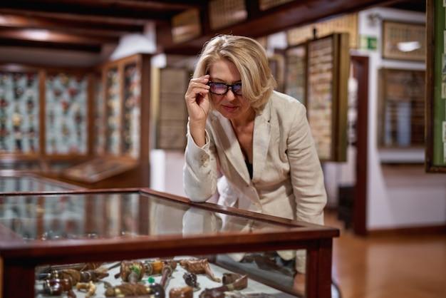 Vue arrière d'une jeune femme de race blanche se tenant dans une galerie d'art devant deux grandes peintures colorées