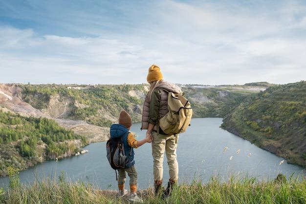 Vue arrière d'une jeune femme routard et d'un petit garçon tenant par les mains tout en se tenant devant le lac entouré de montagnes pendant le voyage