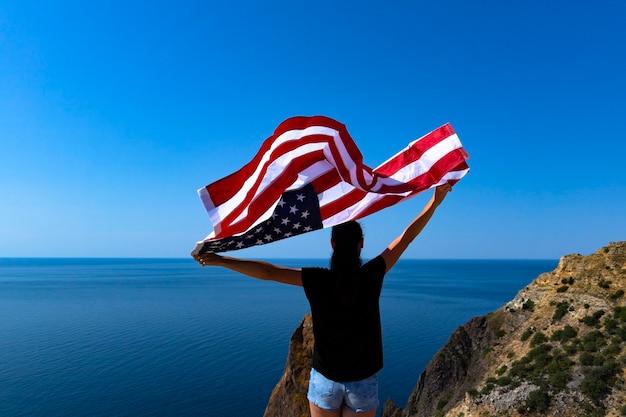 Vue arrière d'une jeune femme tenant un drapeau américain sur la côte contre la mer lumineuse ensoleillée.