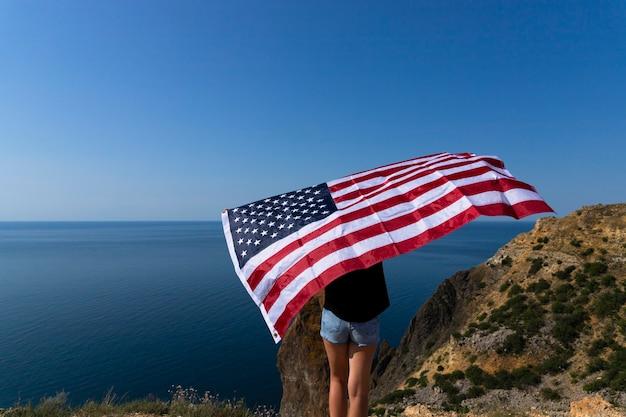 Vue arrière d'une jeune femme tenant un drapeau américain sur la côte contre la mer lumineuse