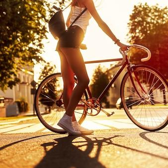 Vue arrière de la jeune femme tenant son vélo au coucher du soleil