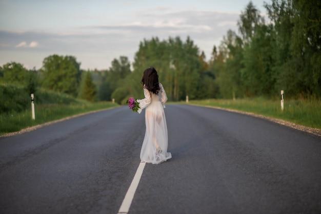 Vue arrière d'une jeune femme vêtue d'une robe sexy blanche, debout sur une ligne de route de campagne asphaltée vide