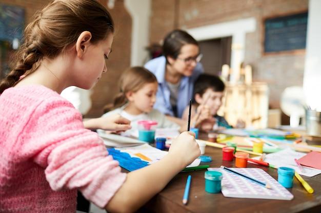 Vue arrière d'une jeune fille peignant en cours d'art