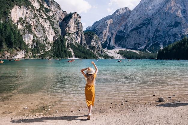 Vue arrière de la jeune fille en robe et plaisancier sur la rive du lago di braies dans les dolomites, italie, europe.