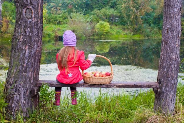 Vue arrière de la jeune fille en veste colorée, assis sur un banc et tenant un grand panier avec des pommes rouges