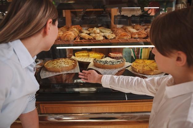 Vue arrière d'un jeune garçon et sa mère à la recherche de desserts à vendre à la boulangerie
