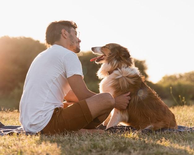 Vue arrière jeune homme avec chien au bord de la mer