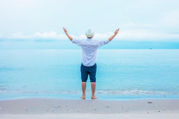 Vue arrière d'un jeune homme décontracté au bord de la mer tenant les deux mains en l'air célébrant la vie et la liberté