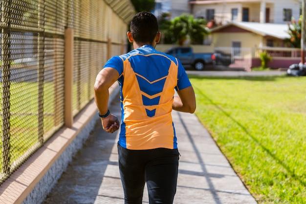 Vue arrière d'un jeune homme faisant du jogging à l'extérieur