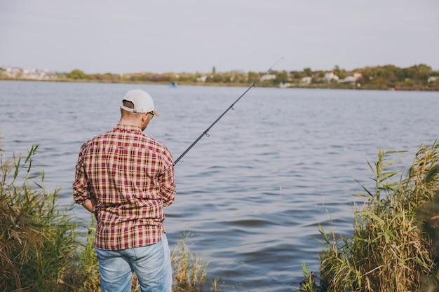 Vue arrière jeune homme mal rasé avec canne à pêche en chemise à carreaux, casquette et lunettes de soleil jette des appâts et pêche sur le lac depuis la rive près des arbustes et des roseaux. mode de vie, loisirs, concept de loisirs de pêcheur.
