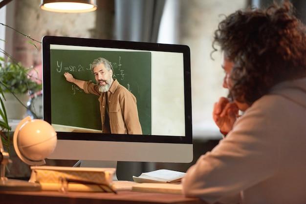 Vue arrière d'un jeune homme regardant un écran d'ordinateur et étudiant en ligne pendant que l'enseignant dit quelque chose et montre du doigt le tableau noir