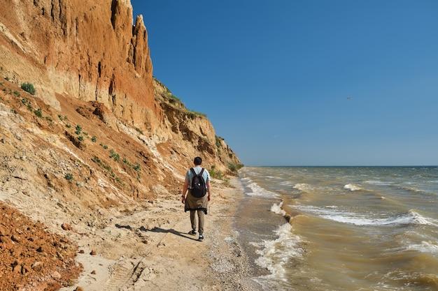 Vue arrière d'un jeune homme et d'un sac à dos marchant seuls le long d'une colline de sable au-dessus de la mer.