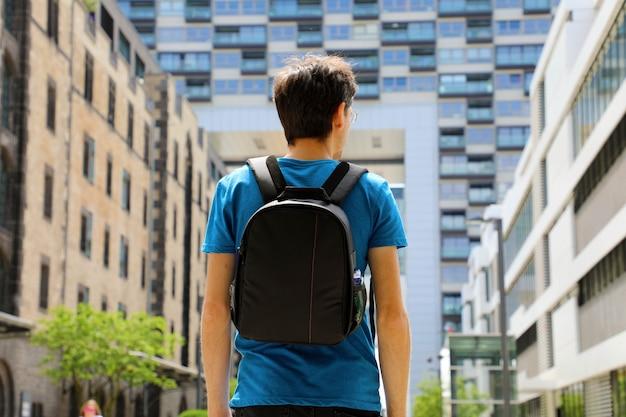 Vue arrière d'un jeune homme avec sac à dos vient d'arriver dans une grande ville et à la recherche de bâtiments modernes avec perspectives et opportunités