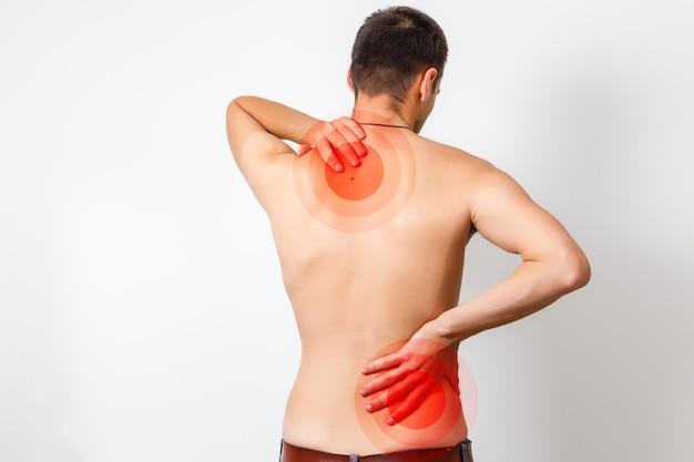 Vue arrière d'un jeune homme tenant son cou dans la douleur, isolé sur fond blanc, photo monochrome avec du rouge comme symbole du durcissement