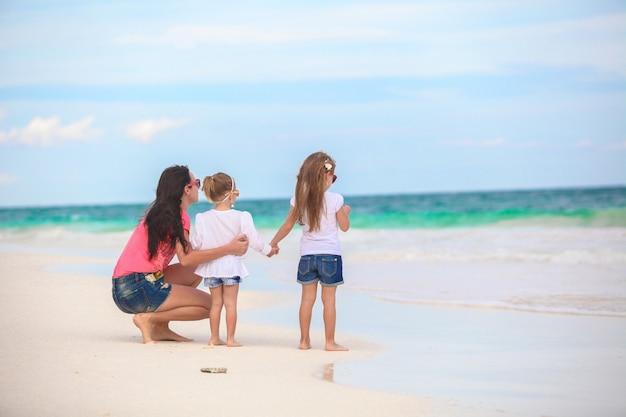 Vue arrière de la jeune maman fashion et deux ses enfants à la plage exotique sur une journée ensoleillée