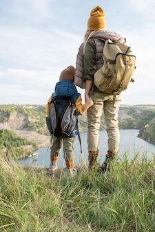 Vue arrière de la jeune mère et du petit fils avec des sacs à dos tenant par les mains tout en se tenant devant le lac entouré de montagnes pendant le voyage