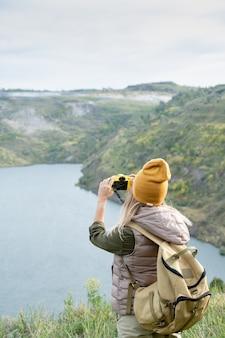 Vue arrière d'une jeune routarde en tenue décontractée chaude avec une caméra photo debout devant le lac pendant le week-end