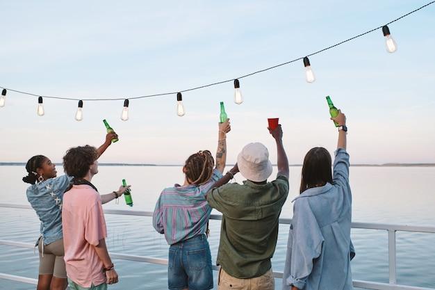 Vue arrière de jeunes amis avec des boissons profitant d'une fête en plein air