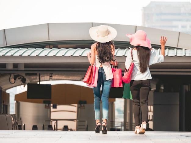 Vue arrière des jeunes femmes avec des sacs à provisions en faisant du shopping